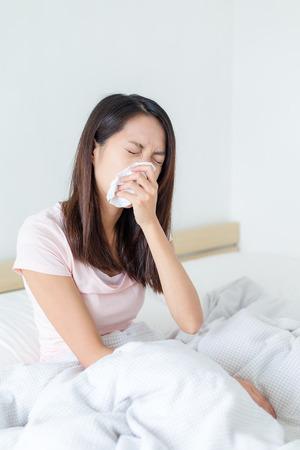 estornudo: La mujer sufre de enfermedad y estornudar en la cama Foto de archivo