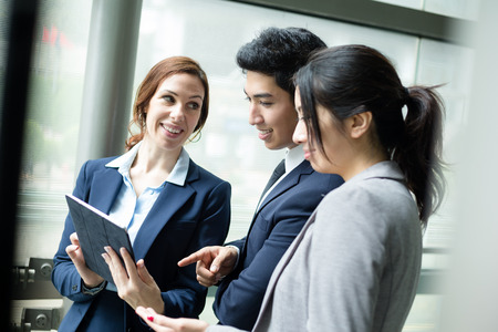 chinese american ethnicity: Business team discuss on digital tablet