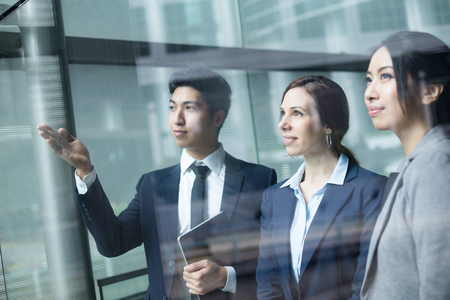 far away look: Group of business people looking though window