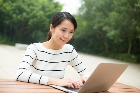 working on computer: Woman working on notebook computer Stock Photo