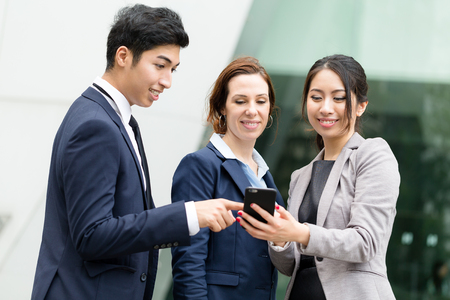 discuss: Business people discuss on cellphone together Stock Photo