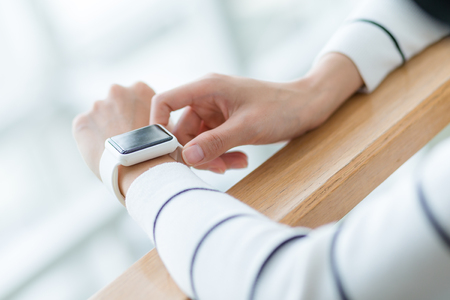 hall monitors: Woman touch on smart watch Stock Photo