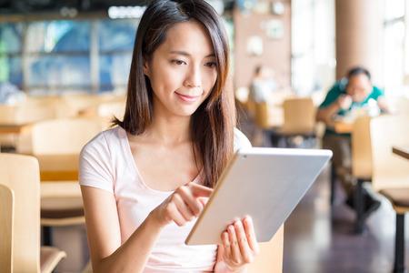 Mujer con tablet PC en el interior del café