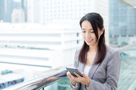 officeworker: Businesswoman looking at mobile phone
