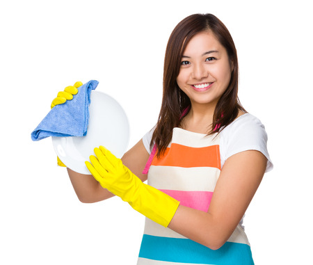 japanese cookery: Young housewife washing dishes with rag