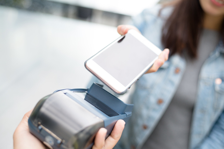 paying: Woman paying with NFC technology on smart phone