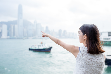 far away look: Woman finger point to the location in Hong Kong island
