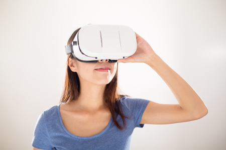 reality: Woman looking though virtual reality device Stock Photo