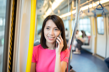 compartment: Woman talk to cellphone at train compartment