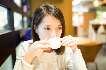 far away look: Woman drink of coffee at cafe