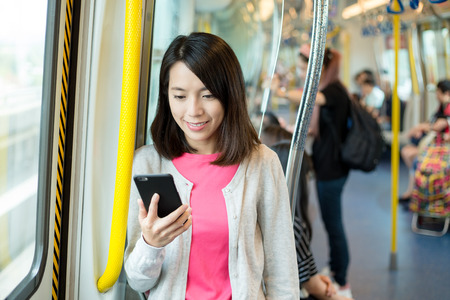 sub station: Woman use of mobile phone at train compartment