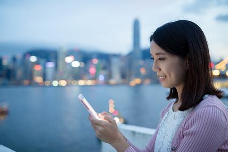 uso de la mujer del teléfono móvil durante la noche Foto de archivo