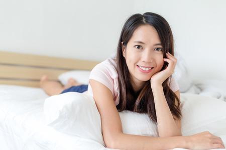 woman lying down: Woman lying down on bed Stock Photo
