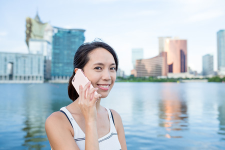 macao: Woman talking to cellphone in Macao city