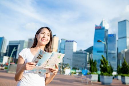 lejos: Mujer que sostiene el mapa de la ciudad y mirando a lo lejos Foto de archivo