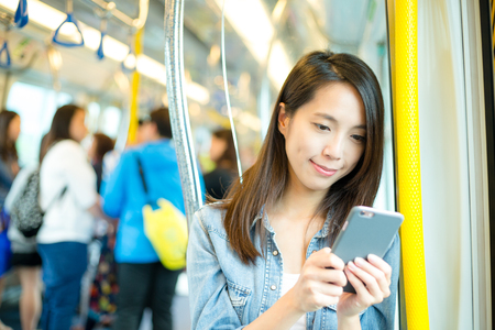 compartment: Woman use of mobile phone inside train compartment