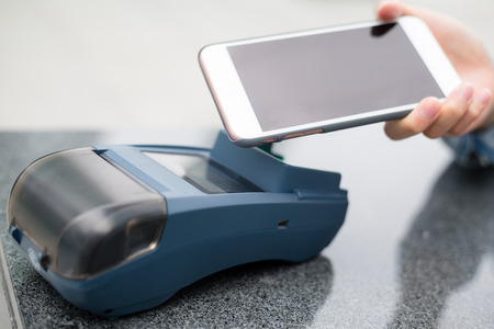 pos: Customer pay with mobile phone on pos terminal Stock Photo