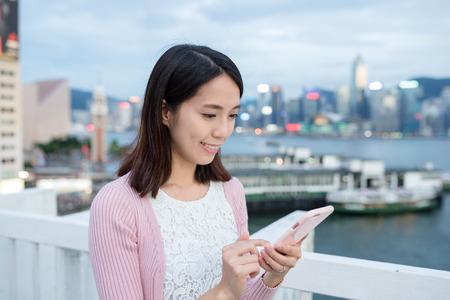 sending: Woman sending sms on cellphone