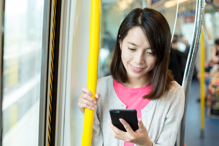 compartment: Woman use of cellphone inside train compartment