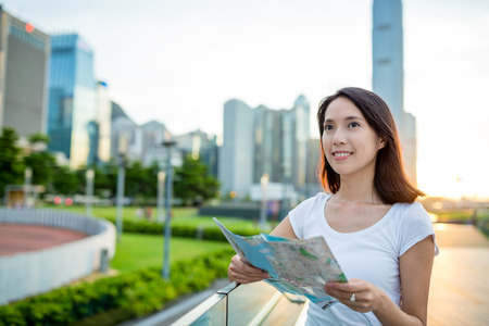 far away look: Woman using city map in Hong Kong at evening