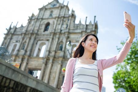 take a history: Woman taking selfie in Macau
