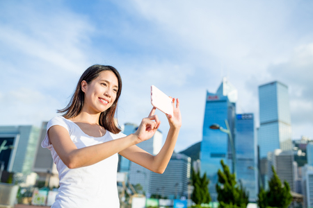 Mujer que usa el teléfono celular para tomar la foto