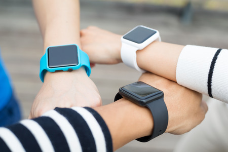 comparing: Athlete comparing time on smart watch with friend Stock Photo