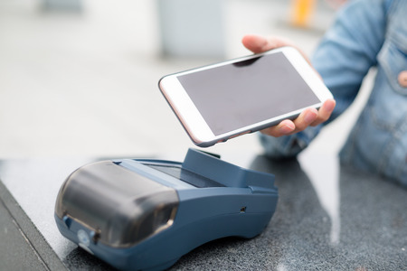 contactless: Woman paying with NFC technology on mobile phone