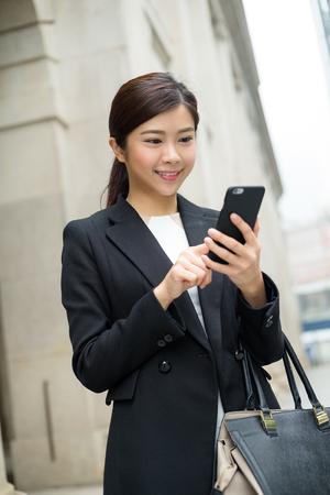 sending: Asian businesswoman sending sms on mobile phone