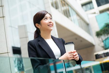 far away look: Businesswoman take a break at outdoor Stock Photo