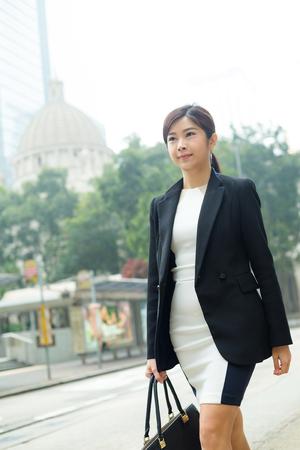 far away look: Business woman walking at street