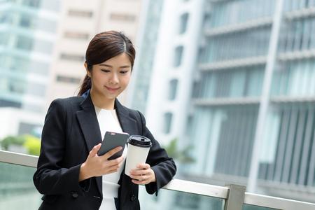 mujeres morenas: Empresaria envío de mensajes con el teléfono inteligente Foto de archivo