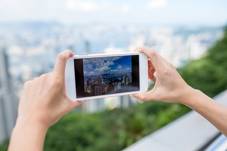 hold on: Woman taking photo on city view of Hong Kong with cellphone