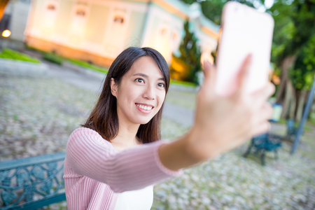 take a history: Woman taking selfie by mobile phone in Macau Stock Photo