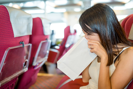 Vrouw onwel gevoel en braaksel op papier zak