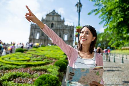 lejos: Mujer que sostiene el mapa de la ciudad y el dedo que señala lejos Foto de archivo