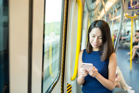 compartment: Woman sending text message inside train compartment