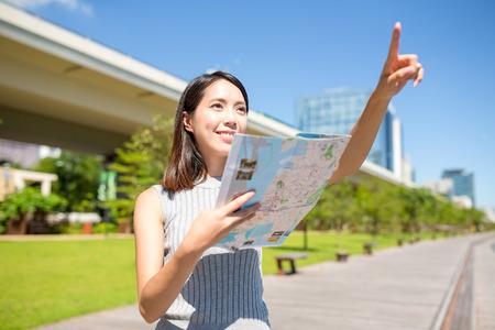 lejos: Mujer que sostiene un mapa y el dedo que señala lejos Foto de archivo