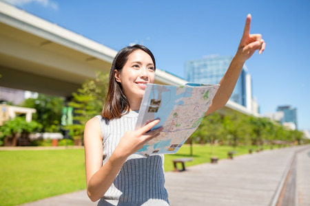 far away: Woman holding a map and finger pointing far away Stock Photo