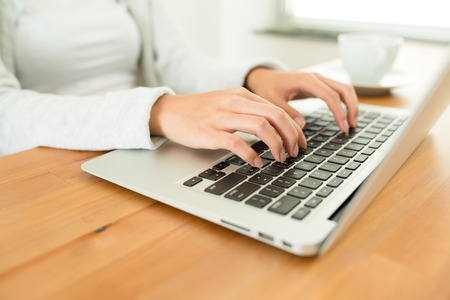 working on computer: Woman working on laptop computer Stock Photo