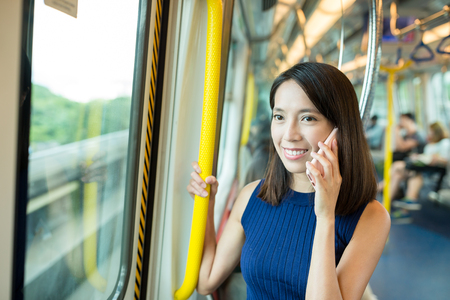 Woman talk to cellphone inside train compartment Stock Photo