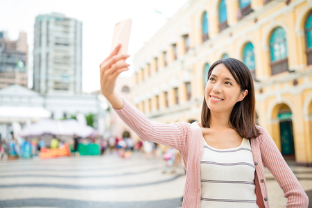 self image: Woman self image by cellphone in Senado Square of Macau Stock Photo