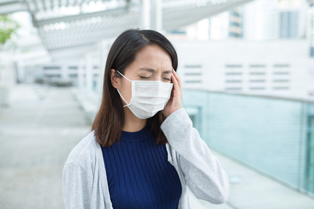 transmissible: Woman wearing face mask for protection at outdoor