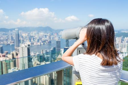 though: Tourist using binocular looking though Hong Kong cityscape