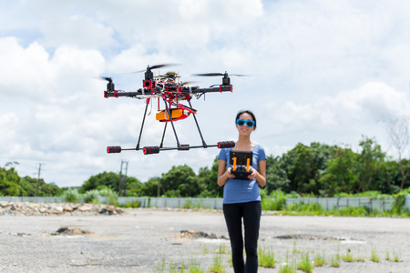 maneuvering: Woman controlling drone quadcopter flying Stock Photo