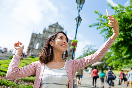 saint pauls cathedral: Woman taking selfie with Saint Pauls Cathedral in Macau Stock Photo