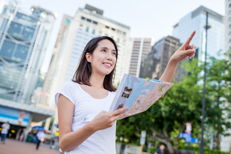 far away: Woman holding city map and finger pointing far away