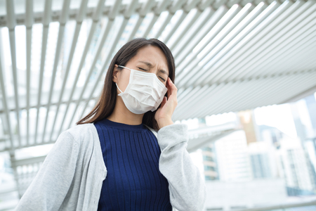 transmissible: Woman wearing face mask at city