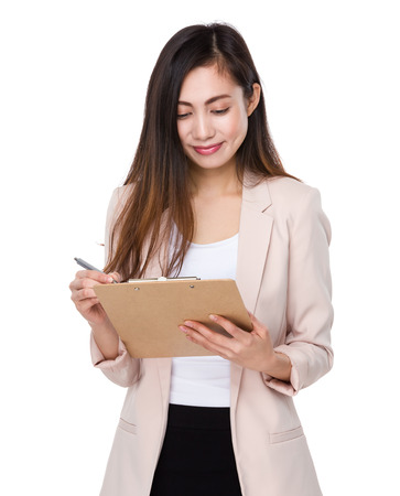 take a note: Businesswoman take note on clipboard Stock Photo