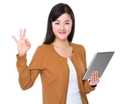 Young Woman hold with tablet and ok sign gesture